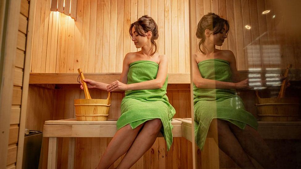 Frau mit grünem Saunatuch in Sauna