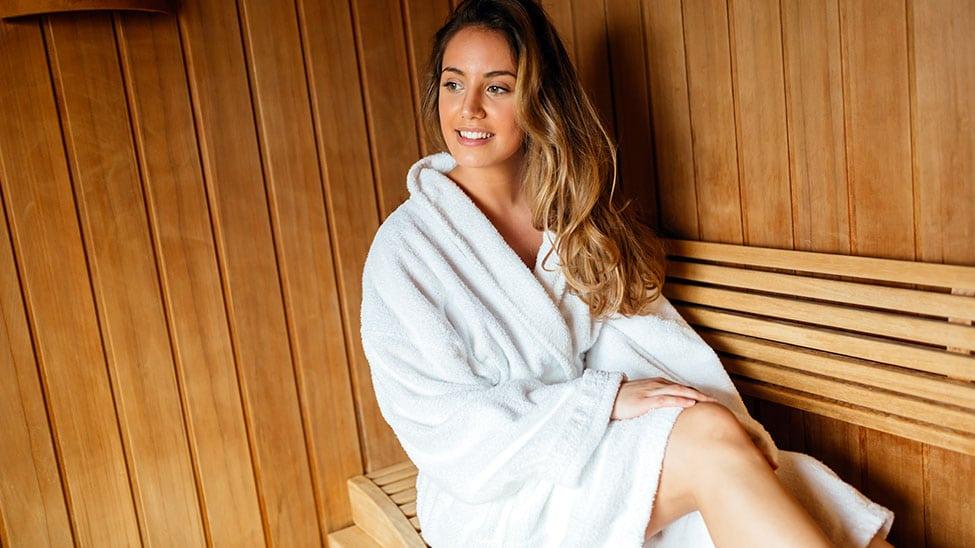 Frau mit weißem Saunatuch in Sauna