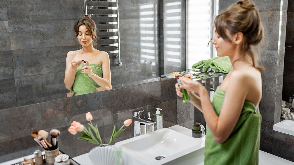 Frau nimmt Tagescreme im Bad auf Hand