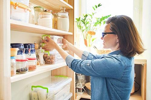 Frau organisiert Haushalt und räumt Regal ein