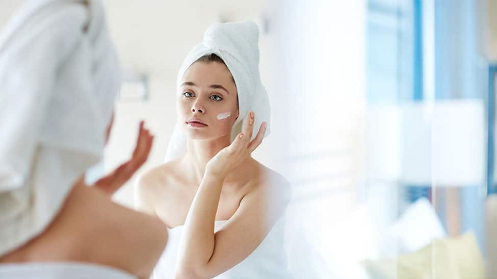 Frau trägt Body Lotion auf Gesicht auf