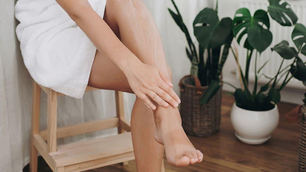 Frau trägt Tagescreme auf Beine auf