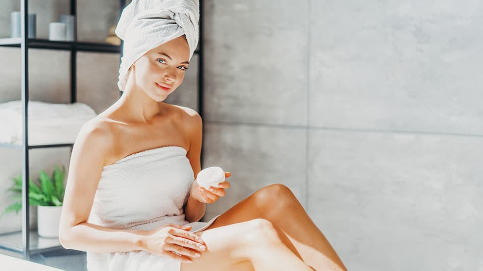 Frau trägt Tagescreme auf Körper auf