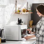 Mädchen nutzt Mikrowelle in Küche