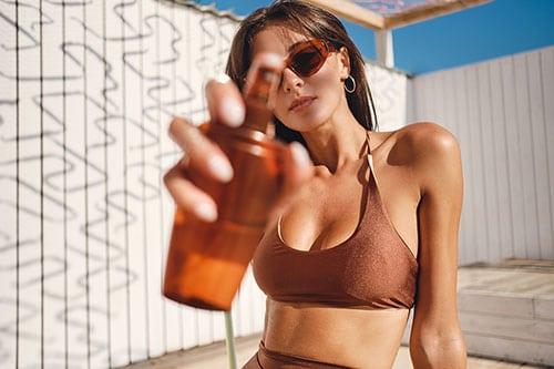 Frau in Bikini sprüht Sonnencreme für Gesicht