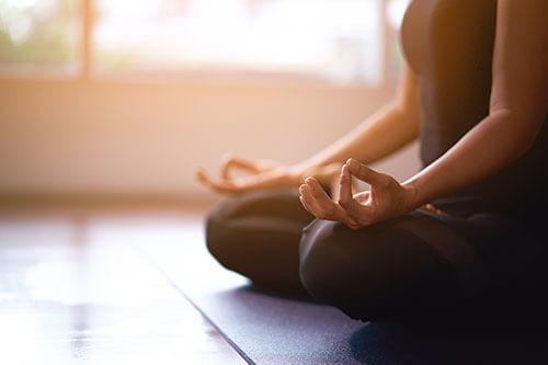Frau meditiert als Entspannungstechnik