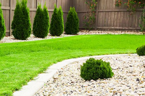 Gartengestaltung mit Rasen, Büschen und Steinen