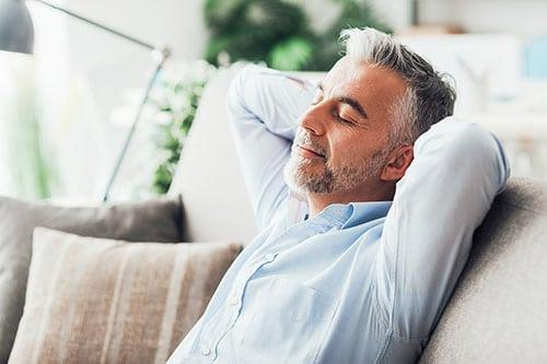Mann sitzt entspannt mit Armen hinter Kopf verschränkt