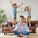 Mutter führt neben ihren Kindern Entspannungstübung in Form von Meditation durch