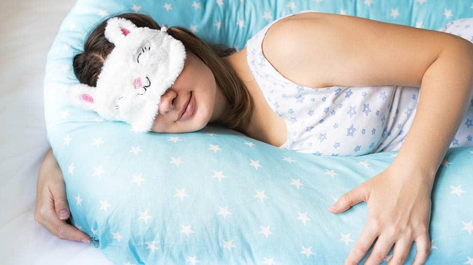 Schwangere schläft mit Seitenschläferkissen